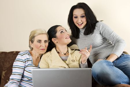 Three happy women having an conversation and  using laptop home sitting in sofa  and relaxing photo