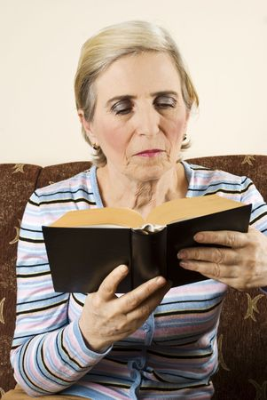 Older woman sitting in her couch and reading a book photo