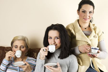 Smiling three women friends sitting in a couch and enjoying a hot drink together photo