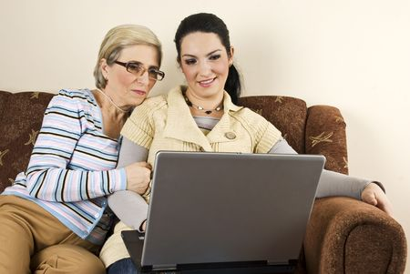 Two women young and old sitting on couch and using laptop  photo