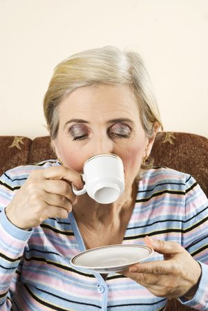 Aged woman drinking a cup of coffee alone and sitting in  a couch photo