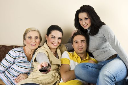 closer: Happy group of friends or family watching tv and smiling