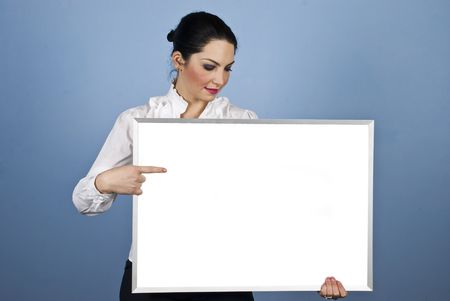 Businesswoman holding a blank white banner ,pointing  and looking down to copy space on blue background photo