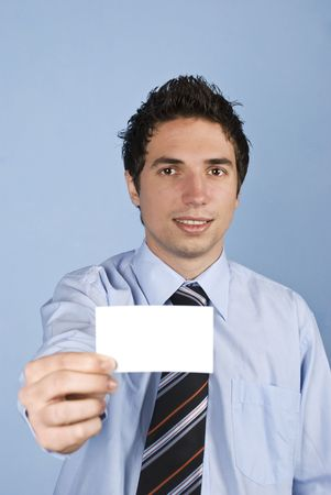 Business man holding a blank business card and smiling in front of blue background photo