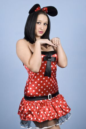 Sexy female dressed in mouse outfit in red with white dots standing in a position with hands  photo