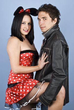 Beautiful young couple,the woman it is dressed in mouse outfit and man in leather jacket and standing  in a sensual position  holding her leg looking at you Stock Photo - 6192006