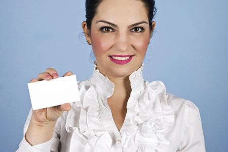 Portrait of smiling young executive woman holding a blank white card on blue background photo