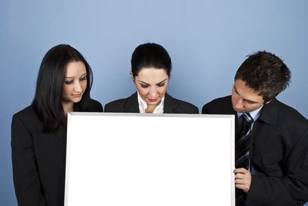 Three business people standing in a line and looking down to banner in front of blue background photo