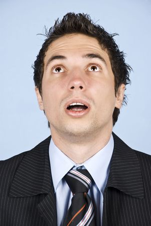 Portrait of amazed businessman with cool hairstyle looking up with mouth open and making big eyes photo