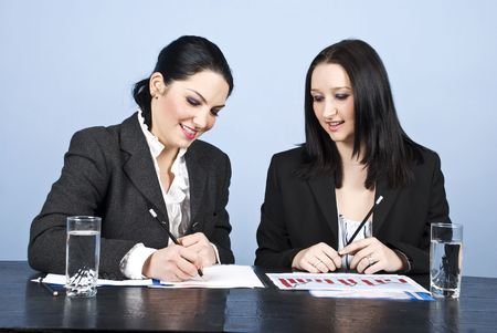 Two business women sitting in office  ,writing on paperwork,laughing and having fun photo