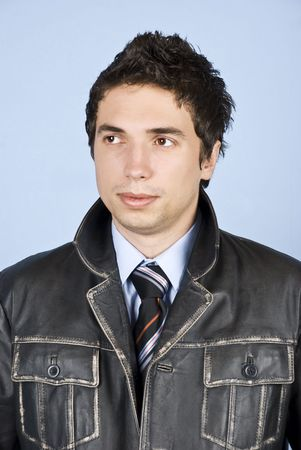 Fashionable young man with cool hairstyle posing in leather jacket and looking away photo