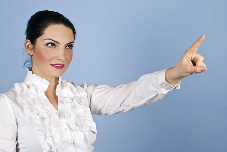 Young smiling business woman pointing up to copy space on blue background photo