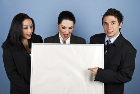 Three people business team holding a blank billboard and the businessman pointing to copy space while the females looking down and being surprised photo