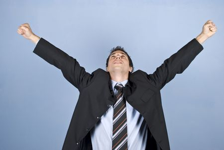 Cheering businessman winning something or having a successful business standing with arms raised and looking up on blue background photo