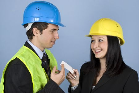 Two young architects having a meeting and both flirting ,the woman giving him a visiting card to calling her photo