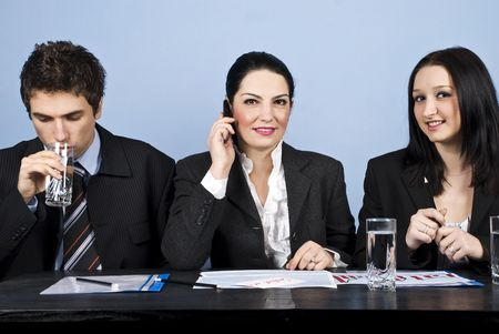 Three business people having a meeting or a conference and all sitting in a line at table,businessman drinking water,a businesswoman speaking at phone mobile and the other woman smiling at you photo