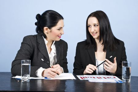Two young business women having an conversation at meeting  photo