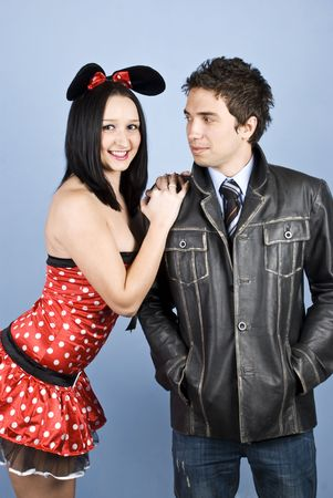 Beautiful young couple posing ,the woman wearing a sexy mouse costume and the man a leather jacket photo