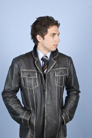 Beautiful young business man in leather jacket looking away in profile and holding hands in pockets photo