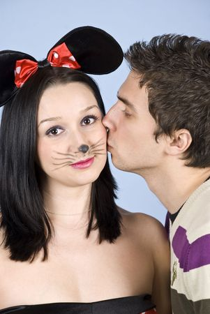 party outfit: Portrait of a young man in profile kissing a woman with mouse ears on her cheek