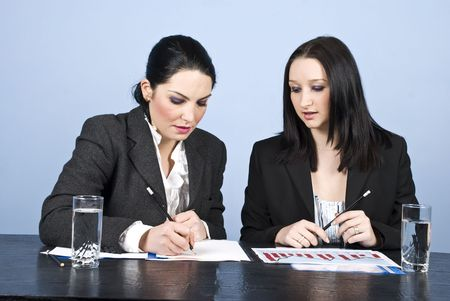 Two businesswomen having a meeting in office and one of them writing on papers and the other reading photo