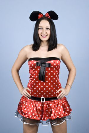 Fashion girl posing in a  sexy mouse costume in front of blue background photo