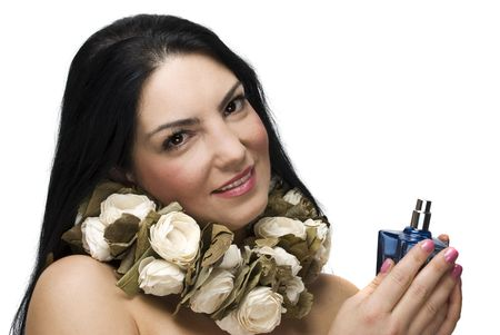 Beautiful brunette woman with many white roses around the neck holding a blue perfume and smiling isolated on white background photo