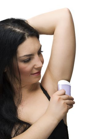 armpits: Brunette woman applying deodorant stick armpits isolated on white background Stock Photo