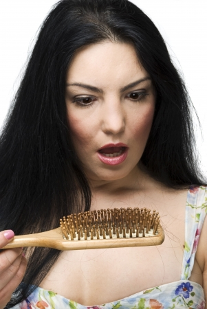 loss: Shocked woman discover how much hair loss on hairbrush,focus on hairbrush isolated on white background Stock Photo