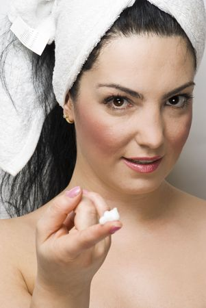 Woman at spa treatment  showing  cream on her finger photo