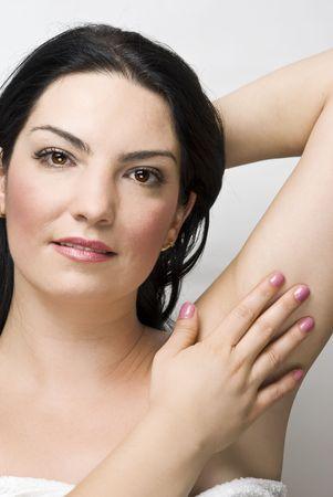 axila: Retrato de mujer hermosa tocar su axila y sonriente, el concepto de piel limpia