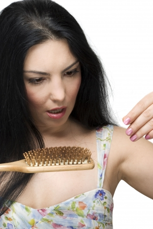 hair problem: Brunette woman with long hair  collecting hairs on the brush hair and being very shocked and scared to lose her hair isolated on white background Stock Photo