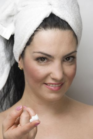 Portrait of young smiling woman showing a finger with cream for skin care,selective focus on finger cream photo