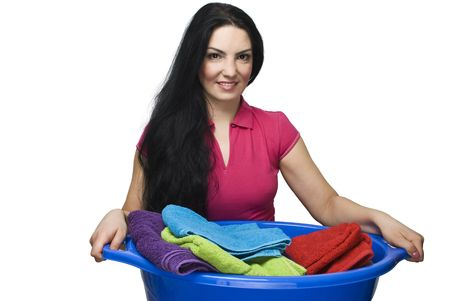 Young brunette smiling woman holding a laundry basket with colorful clean and fresh towels isolated on white background photo