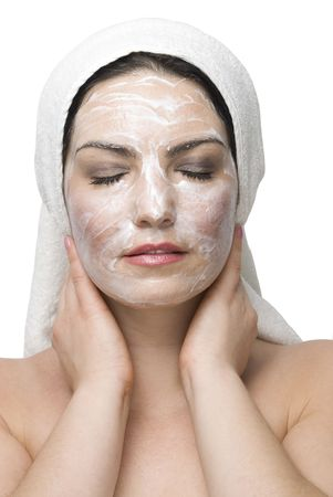Young woman in white bath towel standing with eyes closed  and enjoying a facial mask with cream photo