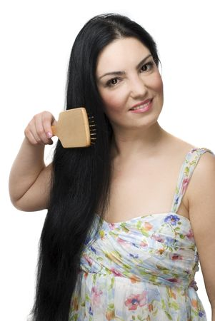 Beautiful woman brushing her long black hair and smiling isolated on white background photo