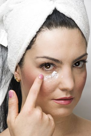 Close up of woman at dayspa applying cream of face  photo