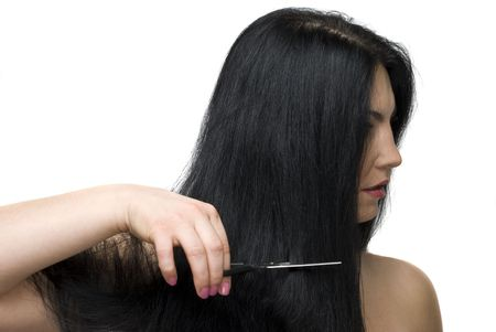 Beautiful brunette woman standing in profile and cutting her long hair with a scissors photo
