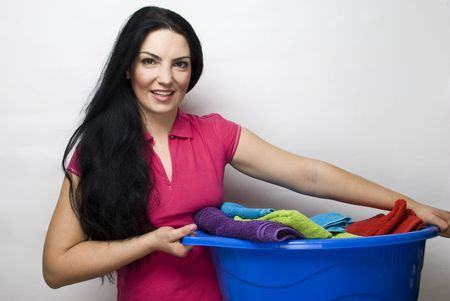 Smiling beauty housewife holding a blue basket with clean laundry  photo
