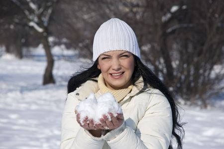 Woman holding snow in hands in a winter sunny day outdoors in park photo