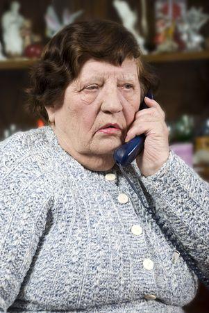80s adult: Anciana hablando en el tel�fono en su hogar y recibir malas noticias Foto de archivo