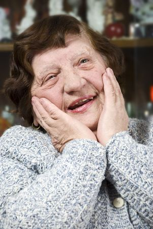 Portrait of happy face of elderly senior woman 80 s laughing and holding hands on her cheeks photo