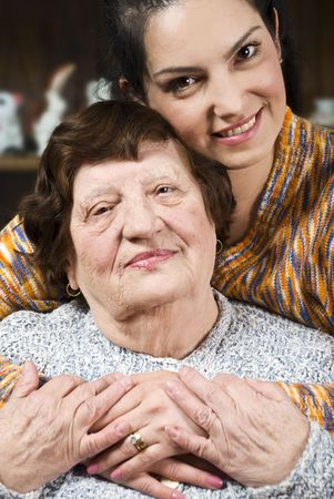 Portrait of a happy grandma and granddaughter sitting in a hug with  their hands together in living room photo