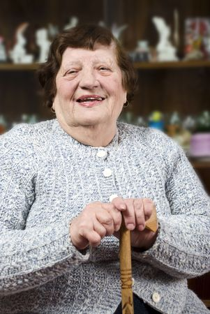 Smiling grandma holding a stick and sitting on chair in her living room photo