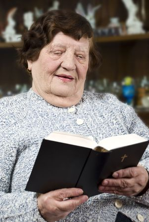 Elderly woman 80s reading bible in her living room and having a positive face photo