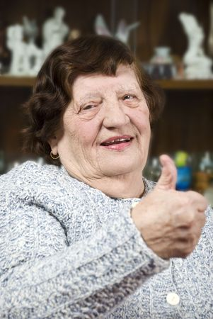 Portrait of elderly woman giving thumbs up and smiling in her living room photo