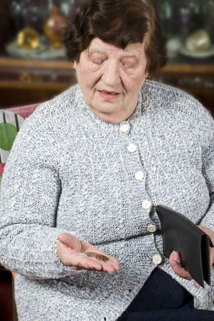 Elderly pensioner sitting on chair in living room and  count last  money from the wallet and holding coins in her hand photo