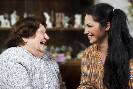 Grandma and her granddaughter having a happy conversation and both laughing together photo