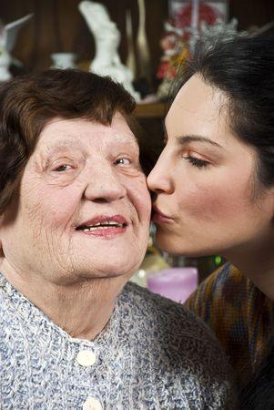 living wisdom: Granddaughter kissing her grandma on cheek and looking surprised