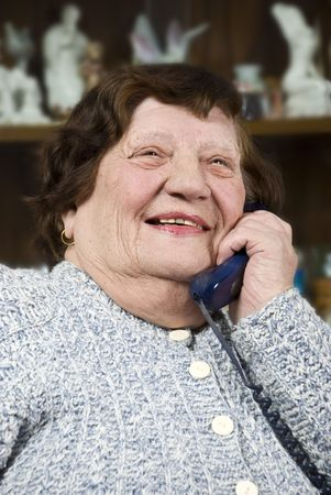 Laughing elderly woman having a funny conversation at telephone in living room photo